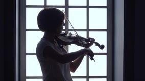 Contra la perspectiva de ventana una muchacha toca el violín Silueta almacen de video