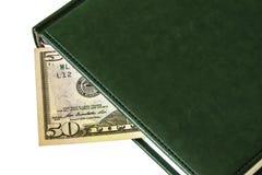 Contra mentiras de um fundo da luz um um diário e a parte de uns 50 dólares Fotografia de Stock