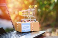 Contra reembolso el comercio electrónico de envío expreso del ordenador portátil que hace compras en línea y el concepto de la or imagen de archivo libre de regalías