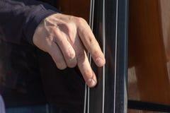 Contrabaixo, mãos que jogam e para largar acima cordas do contrabaixo, fim do jogador do instrumento musical foto de stock royalty free