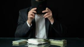 Contrabandista que pone en el pasamontañas, mirando coque y el dinero en la tabla, distribuidor autorizado almacen de metraje de vídeo