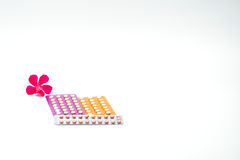 Contraceptieve pillen met roze bloem stock foto's