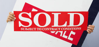 Contract agreed. A real estate sign with sold strip added held up by hands Stock Images