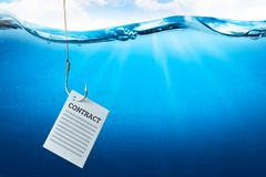 Contract as bait on a fish hook underwater with fish royalty free stock image