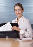 Contract in briefcase. Young businesswoman seating at thr desk in office and holding contract document in briefcase stock image