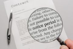 Contract is closely examined with a magnifying glass with the focus on notice periods stock photography