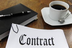 Contract and coffee on a desk Stock Images