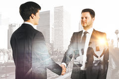 Contract concept. Side view of happy businessmen shaking hands on bright city background with business chart. Contract concept. Double exposure Stock Photo