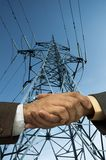 Contract is done. Handshake and electric line,special photo toned f/x,focus point on the center of the photo Royalty Free Stock Photos
