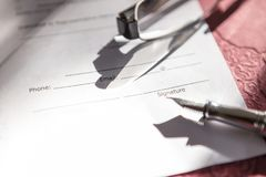 Close-up of Contract form with fountain pen and glasses. Contract form with fountain pen and glasses Royalty Free Stock Images