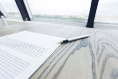 Contract and fountain pen. On office desk near window with panoramic view on city Royalty Free Stock Photos
