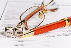 Contract with glasses, pen and dices cubes with words YES NO. Royalty Free Stock Images