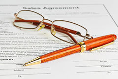 Contract with glasses and wooden pen ready to be signed. Selective focus Stock Photography