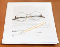 Contract, golden pen and eyeglasses on table Stock Images