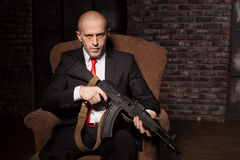 Contract killer holds automatic weapon. Contract killer in suit and red tie sitting in a chair and holds automatic weapon. Brave professional secret agent on Royalty Free Stock Photography