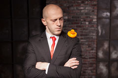 Contract killer shows his fears and secrets. Contract killer in suit and red tie shows his fears and secrets. Special agent holds little toy duck in hand. Hired stock images