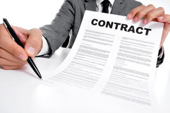 Contract. Man wearing a suit sitting in a table showing a contract and where the signer must sign Stock Photos