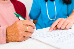Contract with Nursing Home. Nurse helping elderly with contract entering nursing home Stock Photos