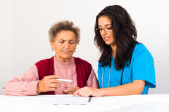 Contract with Nursing Home. Nurse helping elderly with contract entering nursing home Royalty Free Stock Photography