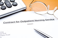 Contract outpatient care service calculator. Contract about a nursing service on an outpatient basis with calculator, reading glasses and ballpoint pen Stock Photos