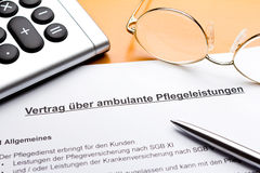Contract outpatient care service german. Contract about a nursing servce on an outpatient basis with calculator, reading glasses and ballpoint pen, german Royalty Free Stock Image