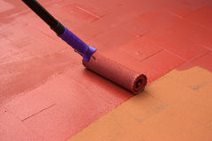 Contract painter painting a floor on color red Royalty Free Stock Image
