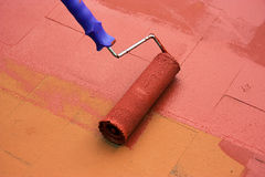 Contract painter painting a floor with a paint roller Royalty Free Stock Photography