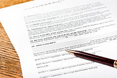 Contract with pen. Signed real estate contract with a pen on an oak desktop Royalty Free Stock Photography