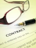 A contract with a pen and glasses. Contract with a pen and glasses royalty free stock images