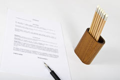 Contract for signature. This image shows a contract for signature with a pen and a cup with pencils Royalty Free Stock Photo