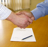 Contract signed. 2 businessmens hands shaking over a signed contract Royalty Free Stock Image
