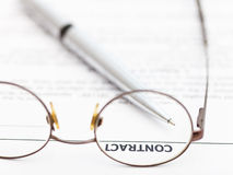 Contract and silver pen through spectacles Royalty Free Stock Images
