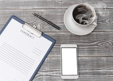 Contract, tablet, pen, smartphone, coffee cup on a wooden background. Concept of signing a contract. business Stock Photos