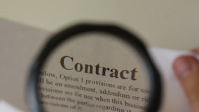 Contract under magnifying glass Royalty Free Stock Image