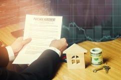 Contract voor de aankoop van een huis De makelaar in onroerend goed houdt de sleutels huismodel en dollars Een huis van twintig p royalty-vrije stock afbeelding