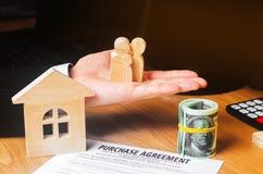 Contract voor de aankoop van een huis De makelaar in onroerend goed houdt de sleutels huismodel en dollars Een huis van twintig p royalty-vrije stock fotografie