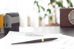 Contract on a wooden desk with clock and fountain Royalty Free Stock Photos