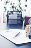 Contract on wooden desk with clock and fountain Stock Photography