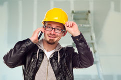 Contractant in Bouwvakker op de Telefoon van de Cel in de Plaats van het Huis Royalty-vrije Stock Foto's