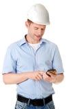 Contractant die in bouwvakker zijn celtelefoon met behulp van Stock Foto