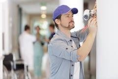 Contractant die kabeltelevisie-camera installeren in het ziekenhuis royalty-vrije stock foto