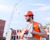 Contractantcontrole volgens plan Mensen oranje vest en de helmwerken bij bouwwerf Controlebouw royalty-vrije stock foto