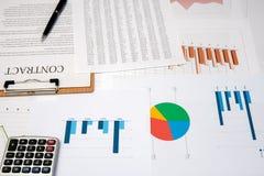Contracten, grafieken, en grafieken op het bureau bedrijfsbureauconcept stock foto's