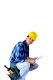 Contractor. A building contractor with tools kneeling on white background stock photography