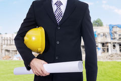 Contractor with blueprint at construction site. Close up of male contractor wearing formal suit and holding a blueprint on the residential construction Royalty Free Stock Photography