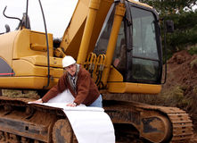 Contractor checking the construction area. Contractor in white hard hat with blueprints in front of heavy equipment Royalty Free Stock Photos