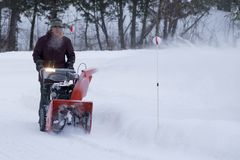 Contractor Clearing Residential Driveway of Snow in Winter. Man clears a driveway of heavy snow with a powerful 24 inch snow blower with rugged tires for added Stock Photo