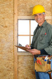 Contractor with Clipboard. A middle aged contractor standing in new construction writing on a clip board. Man is wearing jeans, work shirt, tool belt and a hard Royalty Free Stock Photo