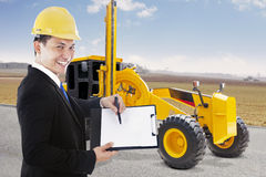 Contractor with clipboard and road grader Royalty Free Stock Images