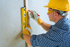 A contractor do layring. On a cocrete wall Royalty Free Stock Photo